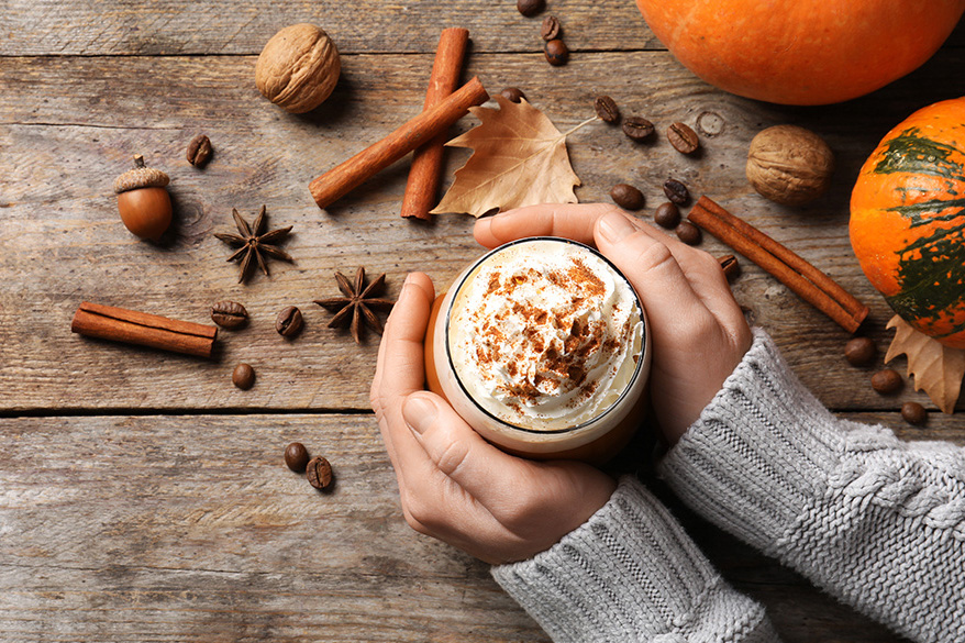 Woman's hand around a pumpkin spice latte, with spices, nuts, leaves and pumpkin